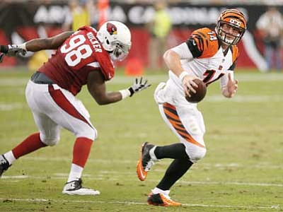 Bengals quarterback Andy Dalton scrambles away from Cardinals' Frostee Rucker during their preseason game Sunday.  (Ross D. Franklin/The Associated Press)