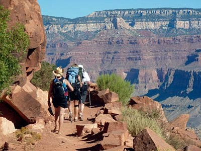 """This Sept. 27, 2010, file photo shows hikers on the South Kaibab Trail in Grand Canyon National Park, Ariz. The Grand Canyon is imposing new restrictions on hikers who are turning up in larger numbers to complete grueling """"rim to rim"""" excursions from one end of the canyon to the other. The popularity of the hikes have created problems with litter and safety as people need to be rescued. (The Associated Press/file photo)"""