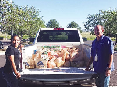 Lockheed Martin Leadership Association Board of Directors members Olga Holmann and Tom Donnan pose beside the truckload of food items collected to donate to the Hungry Kids project. Items will go to students in need in the Humboldt Unified School District. (Courtesy photo)
