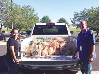 Courtesy photo<br> Lockheed Martin Leadership Association Board of Directors members Olga Holmann and Tom Donnan pose beside the truckload of food items collected to donate to the Hungry Kids project. Items will go to students in need in the Humboldt Unified School District.