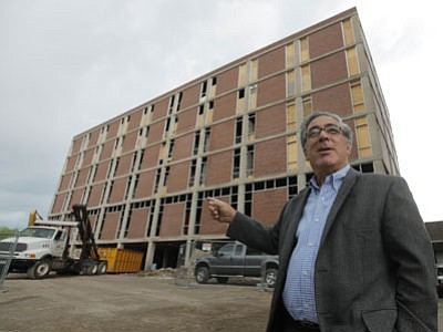 In this June 24, 2010, photo, developer Larry Glazer gestures toward a building to be demolished on Alexander Street in Rochester, N.Y. Glazer and hiw wife, Jane, were aboard their small plane, which took off from the Greater Rochester International Airport, as it flew 1,700 miles down the East Coast on Friday, Sept. 5, 2014, before finally crashing off the coast of Jamaica. (Associated Press photo/Democrat & Chronicle, Carlos Ortiz)