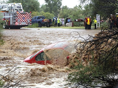 Ron Medvescek, Arizona Daily Star/AP<br>  Water washes over a car after the driver was rescued by members of Northwest Fire District north of Tucson on Monday. The Phoenix and Tucson metro areas were hit by heavy rains, causing flooding and damage. More than 3 inches of rain closed parts of several Phoenix freeways. In Tucson, the National Weather Service recorded nearly 2 inches of rain.