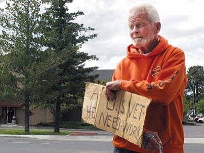 Richard Russler, 77, stands on a corner in Flagstaff Tuesday asking passers-by for financial help. The Flagstaff Police Department has introduced a voucher program to discourage people from giving cash to panhandlers. (Felicia Fonseca/The Associated Press)