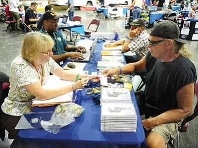 Ruth Funda-lewicz helps Paul Campbell with some benefits paperwork during the Veterans Stand Down homeless services expo at Tim's Toyota Center in Prescott Valley on Tuesday.<br /><br /><!-- 1upcrlf2 -->(Les Stukenberg/The Daily Courier)