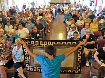 Chase Dunham, 13, a volunteer, holds up a rug for bidders to view during a past Navajo rug auction at the Smoki Museum in Prescott. (Matt Hinshaw/The Daily Courier)