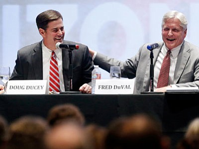 Arizona candidates for governor Doug Ducey (R) and Fred DuVal (D) share a lighthearted moment during a public debate Thursday. (Mike Christy/The Associated Press)