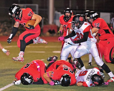 Matt Hinshaw/The Daily Courier<br>Bradshaw's Shane Sorrells (41) leaps over a pack of players Friday night as the Bears hammered Coconino in Prescott Valley.