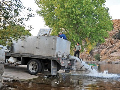 Joe Baynes, City of Prescott parks and rec director, looks on as Lonell Crowther of Crowther's Freshwater Trout of Colorado unloads 700 pounds of rainbow trout into Watson Lake for the second annual Great Outdoors event. (Matt Hinshaw/The Daily Courier)