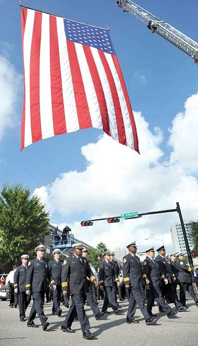 The Florida Times-Union, Bruce Lipsky/The Associated Press<br> Firefighters march under a flag as they approach the fallen firefighters memorial ceremony this weekend in Jacksonville, Fla.