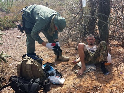 In this June 25, 2014, photo, an unidentified U.S. Border Patrol agent, left, helps an immigrant, including setting up intravenous fluid replacement for dehydration, near Sells, Ariz. The number of migrants who died or needed rescue while crossing the desert from Mexico into Arizona has dropped significantly this year. (Astrid Galvan/Associated Press)