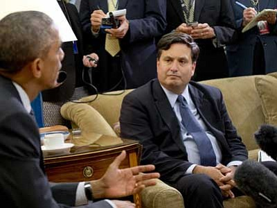 Reporters take notes as Ebola coordinator Ron Klain listens to President Barack Obama speak to the media about the government's Ebola response in the Oval Office of the White House in Washington. (AP Photo/Jacquelyn Martin, File)
