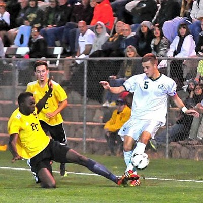Matt Hinshaw/The Daily Courier<br>Phoenix's Anthony Tokpah (9) kicks the ball away from Yavapai's Niall Logue (5) Thursday night during their NJCAA Region 1 semifinal at Ken Lindley Field in downtown Prescott.