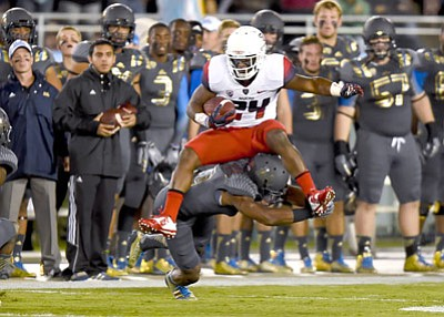 Gus Ruelas/The Associated Press<br>Arizona running back Terris Jones-Grigsby goes up and over UCLA defensive back Fabian Moreau for a first down Saturday in Pasadena.