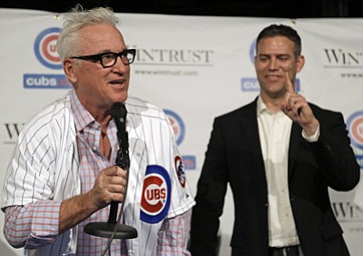 M. Spencer Green/The Associated Press<br>New Cubs skipper Joe Maddon, left, offers to buy a round of drinks after being named manager of Chicago at The Cubby Bear across the street from Wrigley Field on Monday as Theo Epstein, president of baseball operations tells him only one round.