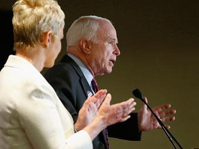 Arizona Republican Sen. John McCain, right, speaks to a crowd as wife Cindy McCain applauds her husband at election night festivities Tuesday, Nov. 4, 2014, in Phoenix. (Associated Press photo/Ross D. Franklin)