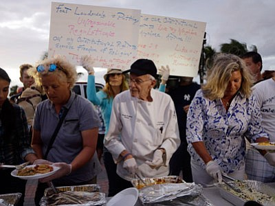 Homeless advocate Arnold Abbott, 90, director of the nonprofit group Love Thy Neighbor Inc., center, serves food to the homeless with the help of volunteers from a public parking lot next to the beach Wednesday, Nov. 5, 2014, in Fort Lauderdale, Fla. (Lynne Sladky/The Associated Press)