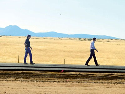 Mike and Jason Fann walk the newly-laid asphalt of what will be the southbound lanes of Highway 89 as work progresses Thursday on the widening project between Prescott and Chino Valley. (Les Stukenberg/The Daily Courier)