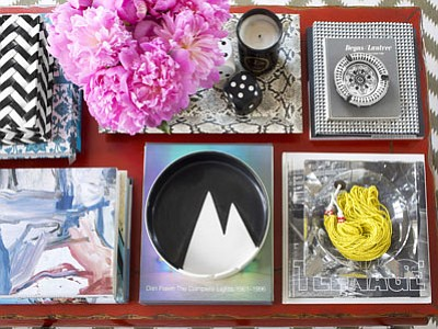 In this photo provided by Burnham Design, homeowners who love having lots of items on hand but don't want their coffee table to look cluttered can take inspiration from this tabletop designed by Max Humphrey of Burnham Design in Los Angeles. Humphrey uses decorative trays to corral items and bring a sense of organization to this very full, colorful table. (Associated Press photo/Burnham Design, Sarah Dorio)