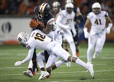 Roy Wayrynen/The Associated Press<br>Oregon State receiver Jordan Villain (13) is tackled by ASU defenders James Johnson (18) and Lloyd Carrington during Saturday night's second quarter in Corvallis, Oregon.
