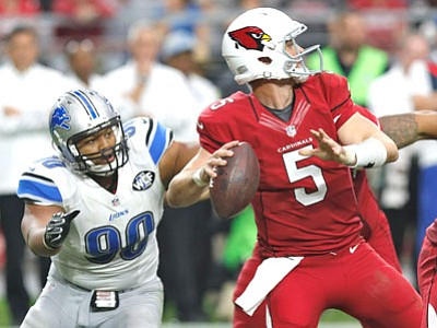Arizona Cardinals quarterback Drew Stanton looks to pass under pressure from Detroit Lions defensive tackle Ndamukong Suh (90) during the first half of Sunday's game. (Ross D. Franklin/The Associated Press)