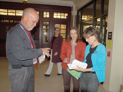 Courts Administrator Rolf Eckel, left, consults with attorney Angela Bradshaw Napper, center, and Prescott Library Manager Public Services Martha Baden, right, about the Book Nook that was unveiled at the Yavapai County Courthouse on Thursday morning. (Cindy Barks/The Daily Courier)