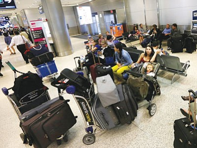 Travelers wait to board their flights at Miami International Airport on Tuesday. Thanksgiving travelers along the East Coast were heading out early because of a forecast calling for a nor'easter that will bring rain and snow. (Alan Diaz/The Associated Press)