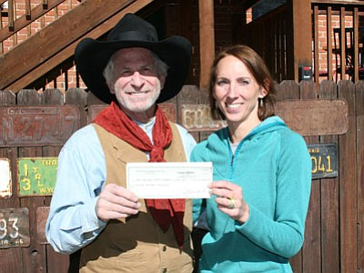 Dave Michelson, owner of the Palace, presents a check to Joellyn Nusbaum, vice president of United Animal Friends. (Courtesy photo)