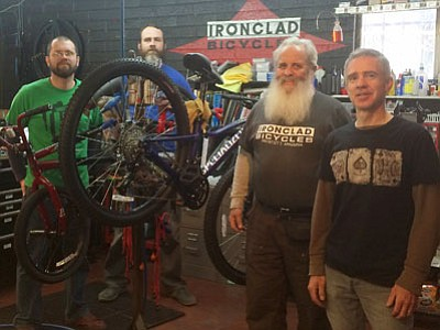 Corey Reese and Mike Hanna step away from repairs Tuesday, Nov. 25, with shop owner Jim Knaup and manager Tim Hull at Ironclad Bicycles. (Les Bowen/The Daily Courier)