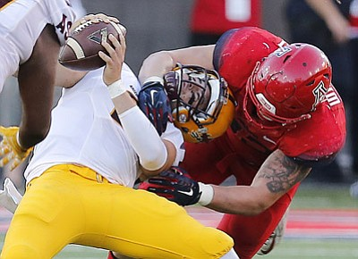 Rick Scuteri/The Associated Press<br>UA linebacker Scooby Wright III, right, sacks ASU quarterback Mike Bercovici during the second half Friday in Tucson.