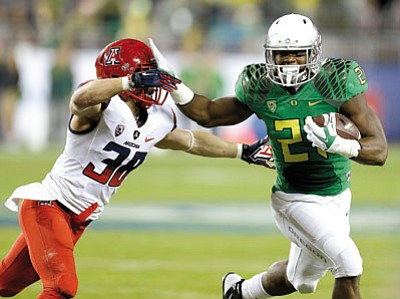 Ben Margot/The Associated Presss<br>Oregon's Royce Freeman, right, evades the tackle of Arizona's Jared Tevis during Friday night's first half in Santa Clara, California.