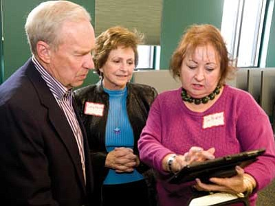 Les Stukenberg/The Daily Courier<br> The Tribute Fence Preservation Project co-directors Jan Monroe and Dottie Morris show John Marsh the online virtual museum of all the memorabilia from the Station 7 fence at a reception Friday at the Prescott Library. Marsh is the father of Granite Mountain Hotshot Superintendent Eric Marsh, who perished with his crew on June 30, 2013 during the Yarnell Hill Fire.