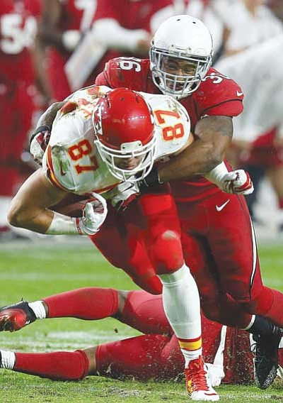 Ross D. Franklin/The Associated Press<br> Arizona Cardinals' Deone Bucannon gets a hand on the ball as Kansas City Chiefs' Travis Kelce runs with the ball during their game Sunday in Glendale. The Cardinals defeated the Chiefs 17-14.