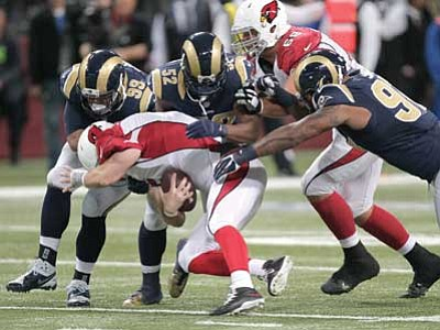 Tom Gannam/The AP<br> Cardinals quarterback Drew Stanton is sacked by, from left, Rams defensive tackle Aaron Donald, outside linebacker Alec Ogletree and defensive end Eugene Sims during their game Thursday. Stanton was injured on the play and left the game.