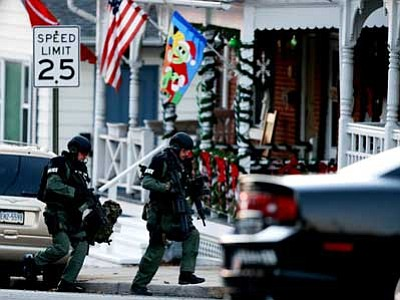 Matt Rourke/The Associated Press<br> Police gather near a home Monday in Pennsburg, Pa., where suspect Bradley William Stone is believed to have barricaded himself inside after shootings at multiple homes. The man remains at large, authorities said.