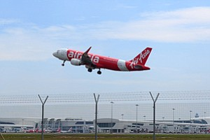 In this May 9, 2014 photo, an AirAsia A320-200 plane takes off from Kuala Lumpur International Airport 2 in Sepang, Malaysia. An AirAsia plane with 161 people on board lost contact with ground control on Sunday, Dec. 28, 2014, while flying over the Java Sea after taking off from a provincial city in Indonesia for Singapore, and search and rescue operations were underway. AirAsia, a regional low-cost carrier with presence in several Southeast Asian countries, said in a statement that the missing plane was an Airbus A320-200 and that search and rescue operations were in progress. The plane in this photo is the same model but not the one which went missing in Indonesia Sunday. (AP Photo/Joshua Paul)