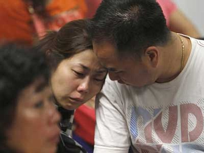 Trisnadi/The AP<br> A relative of the passengers of AirAsia flight QZ8501 weeps as she waits for the latest news on the missing jetliner at a crisis center set up by local authority at Juanda International Airport in Surabaya, East Java, Indonesia, Sunday.