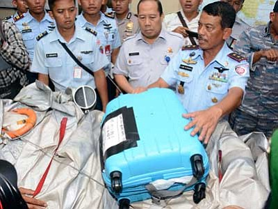Dewi Nurcahyani/The AP<br> Commander of 1st Indonesian Air Force Operational Command Rear Marshall Dwi Putranto, right, shows airplane parts and a suitcase found floating on the water near the site where AirAsia Flight 8501 disappeared Tuesday. Bodies and debris seen floating in Indonesian waters, painfully ended the mystery of AirAsia Flight 8501.