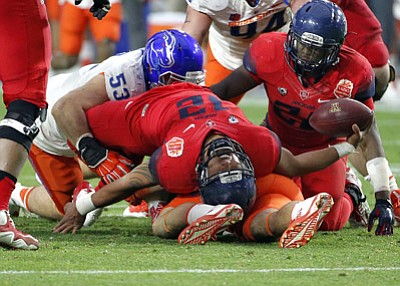 Ross D. Franklin/The Associated Press<br>Arizona quarterback Anu Solomon (12) falls backwards after being hit by Boise State defensive end Beau Martin (53) during Wednesday's first half of the Fiesta Bowl in Glendale.