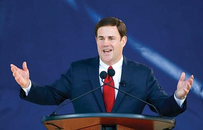 Ross D. Franklin/The Associated Press<br>Republican Arizona Gov. Doug Ducey speaks to the crowd after being sworn in Monday in Phoenix.