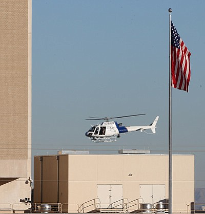 A Department of Homeland Security helicopter flies over the El Paso VA and Beaumont Army Medical Center campus during the search for a gunman in El Paso, Texas on Tuesday, Jan. 6, 2014. (AP Photo/The El Paso Times, Victor Calzada)