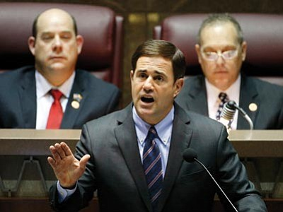 Ross D. Franklin/The Associated Press<br>Arizona Republican Gov. Doug Ducey, front, gives his state-of-the-state address as Arizona House speaker David Gowan, left, and Arizona Senate President Andy Biggs, right, listen at the Arizona Capitol Monday in Phoenix.
