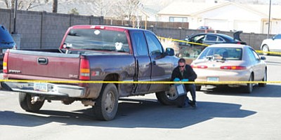 Les Stukenberg/The Daily Courier<br /><br /><!-- 1upcrlf2 -->Prescott Valley Police collect evidence from an alleged vehicular assault at the DES building in the 3200 block of Bob Drive in Prescott Valley on Wednesday afternoon.