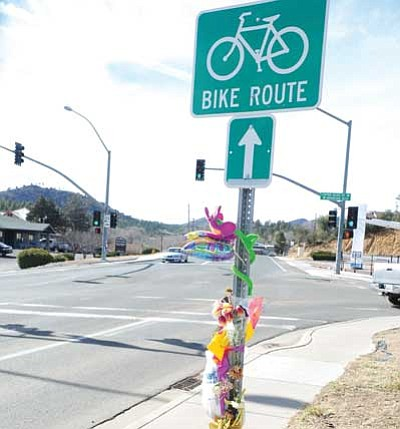 "Les Stukenberg/The Daily Courier<br> Flowers and mementos decorate the Bike Route sign near the intersection of Copper Basin and White Spar roads in Prescott. The site is where Amber ""Cricket"" Harrington was killed on Jan. 16 while riding her bicycle."