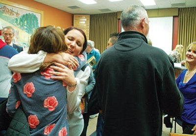 Cindy Barks/The Daily Courier<br> Hotshot widow Amanda Misner, center, receives a congratulatory hug Friday afternoon, after the Prescott Board of the Public Safety Personnel Retirement System voted unanimously that she and fellow widow Roxanne Warneke should receive survivor retirement benefits.