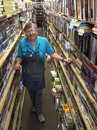 Jason Wheeler/The Daily Courier. Book Nook owner Marilyn Unruh stands amid an aisle of books. Book Nook has about 40,000 books.