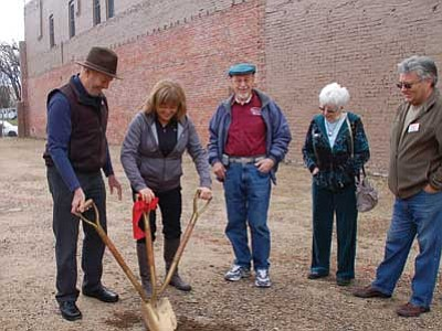 Cindy Barks/The Daily Courier<br> Property owners Howard and Nancy Hinson, above, take the first shovelful of dirt Monday morning on the Holiday Courtyard project, planned for the site of the 2012 Whiskey Row Fire, while Tim Graham, right, and Prescott Chamber ambassadors/volunteers Don and Annette Schiller look on.