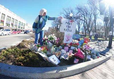 """Les Stukenberg/The Daily Courier<br>Marty Ducharme looks at the makeshift memorial for Kayla Mueller at the intersection of Gurley and Montezuma streets Friday, in downtown Prescott. Ducharme said """"I didn't know her, but she sounds like an amazingly unbelievable person. She inspires me, I will do what I can for other people."""""""