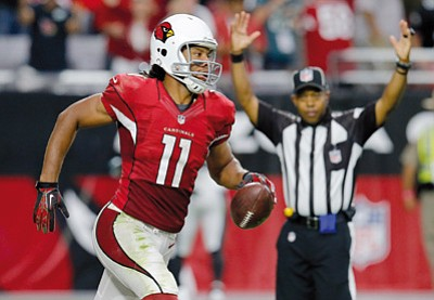 Rick Scuteri/The Associated Press, file<br>In this Oct. 26, 2014, file photo, Cardinals wide receiver Larry Fitzgerald (11) scores a touchdown against the Eagles in Glendale. Fitzy has agreed to a two-year deal that will keep him with Arizona.