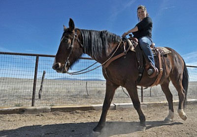 Darlene Wood rides her horse Reno around her property recently in Chino Valley.  Wood had a knee replacement done by orthopaedic surgeon Dr. Mark Davis in March of 2014. Matt Hinshaw/The Daily Courier