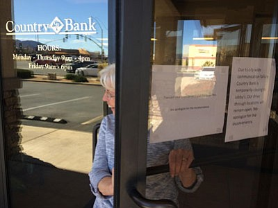 An employee at Country Bank  on Glassford Hill Road in Prescott Valley opens the door for a co-worker. The bank closed its lobby due to the communications outage, but continued to process transactions at drive-thru windows. (Les Stukenberg/The Daily Courier)